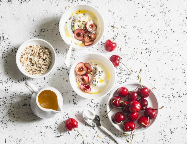 Greek yogurt with cherries and honey  on white table, top view. Flat lay. Summer breakfast or snack