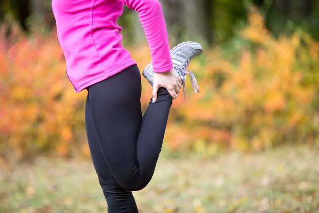 Warming up outdoors in the fall. Quadriceps standing