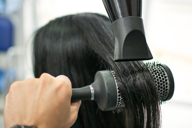 Hairdressers drying long hair with blow dryer and round brush.