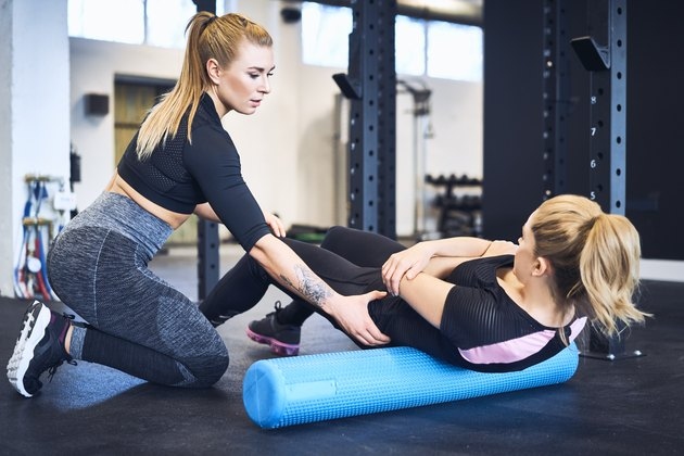 Woman massages muscles with personal trainer after gym workout