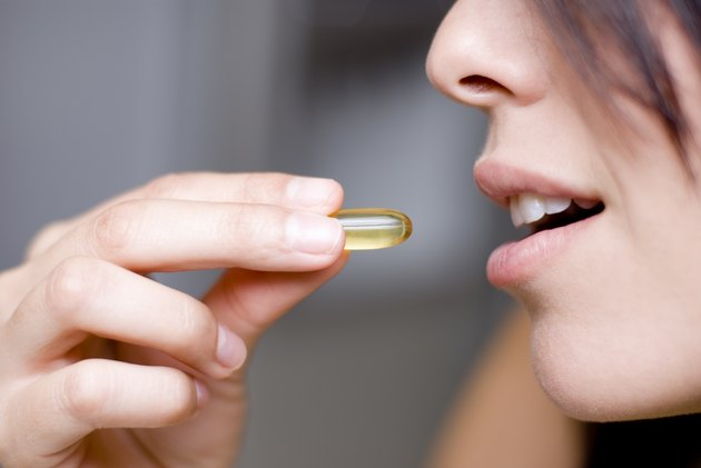 Woman taking vitamin D pill