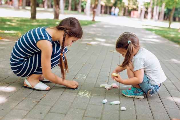 Two girls sitting and drawing with chalk on asphalt in park at normal heights and weights