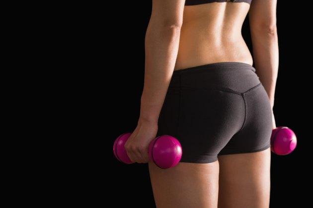 Rear view of slim woman wearing sportswear holding pink dumbbells
