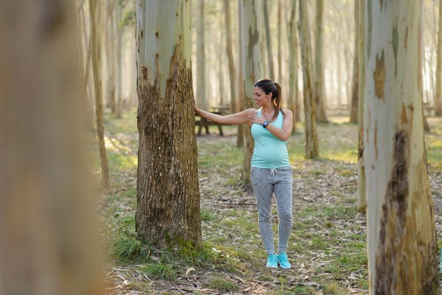 Pregnant healthy woman on fitness outdoor workout stretching chest