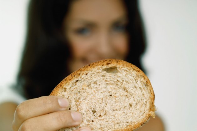 Young woman holding a piece of bread close-up, selective focus, focus on bread