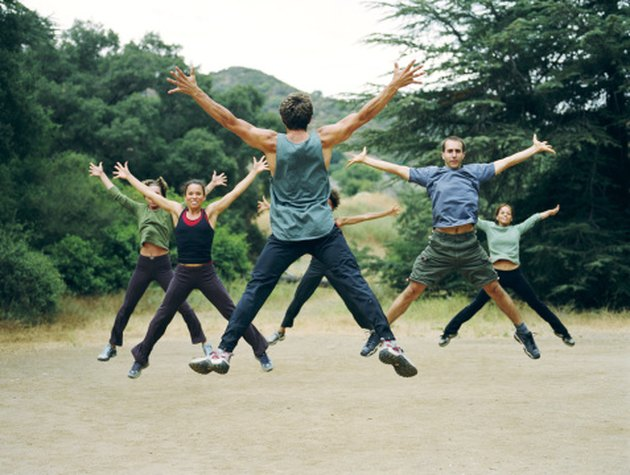 People doing jumping jacks in a park