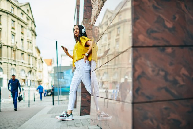 Pondering young hipster girl dressed in stylish clothing looking away while listening to radio station using application on telephone.Pensive brunette woman strolling at urban setting with cellular