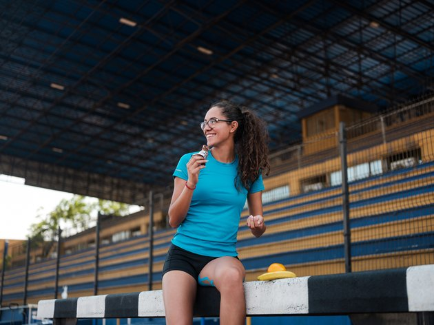 nutrition for athletes athletic woman eating a protein bar