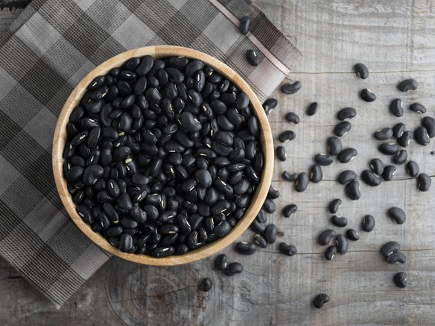Black beans in a wooden bowl, black beans in a wooden spoon on a wood background