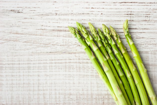 Sprigs of fresh asparagus on a wooden table.