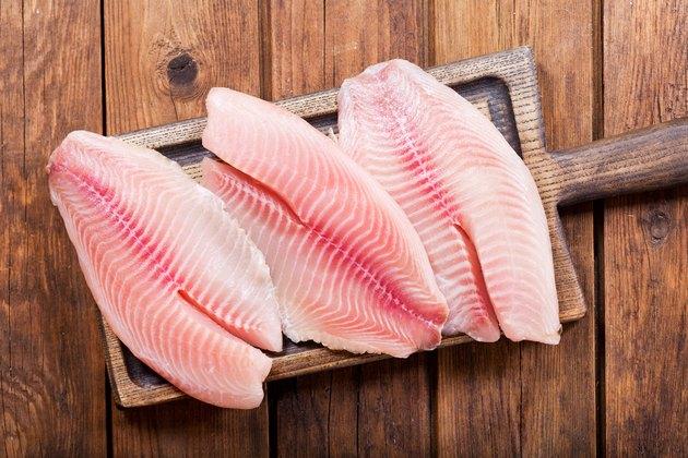 fresh fish fillet on wooden board