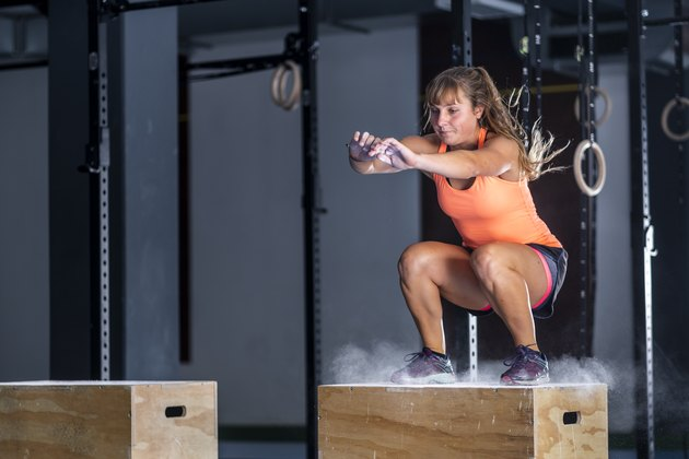 Athletic young woman doing box jump exercise at gym