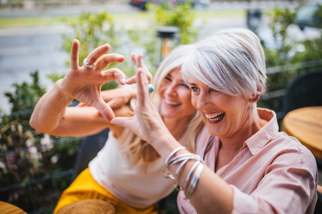 Smiling mature women making heart shape with fingers