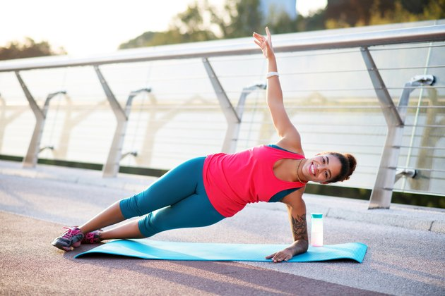 Smiling woman doing side plank while finishing workout