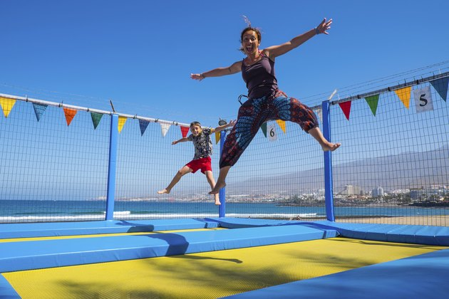 Playful mother and son bouncing on trampoline at the coast
