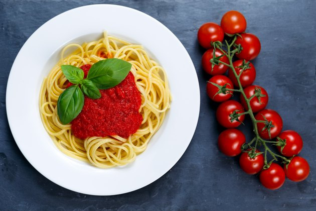 Spaghetti with marinara sauce and basil leaves on top