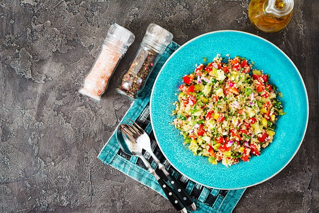 Salad with quinoa, arugula, sweet peppers, tomatoes and cucumber in bowl on a dark background. Healthy food, diet, detox and vegetarian concept. Tabbouleh salad. Top view. Flat lay