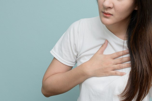 Midsection Of Woman With Chest Pain Against Blue Background