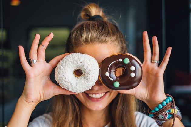 Happy woman holding doughnuts
