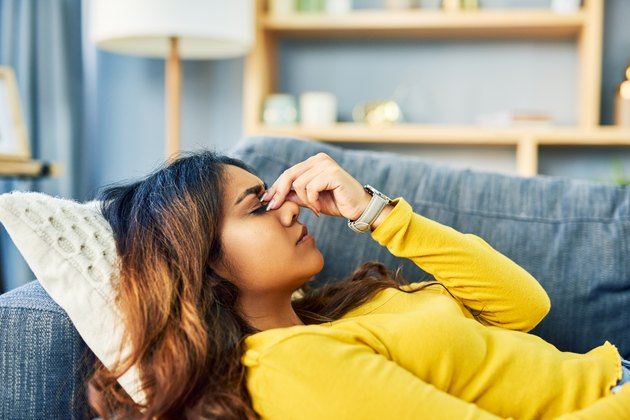 woman wearing yellow sweater lying down on couch holding head with headache