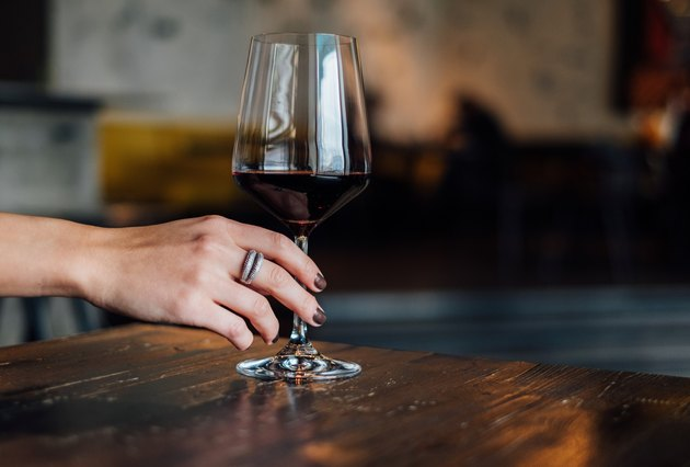 Close-Up Of Hand Holding glass of red wine On wooden Table