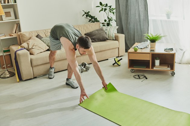 Contemporary sportsman putting mat on the floor while going to do yoga exercises