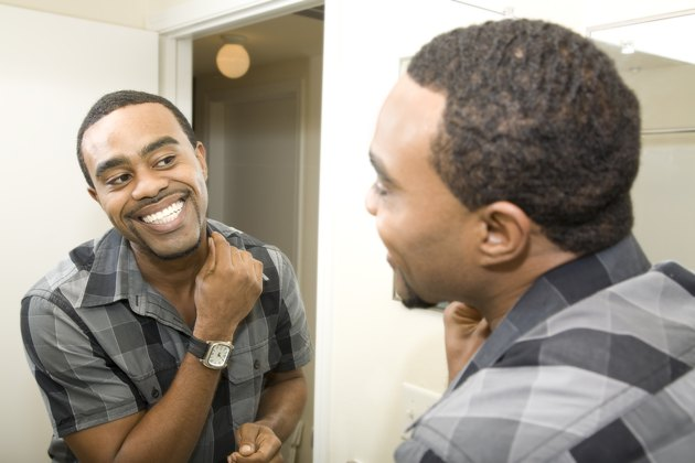Smiling Young Man Getting Ready in front of Bathroom Mirror