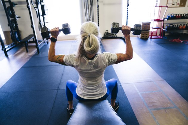 Woman doing seated dumbbell workout for shoulders