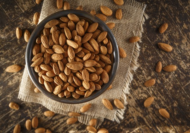 overhead shot of raw Protein-rich Almonds in a bowl on wooden table