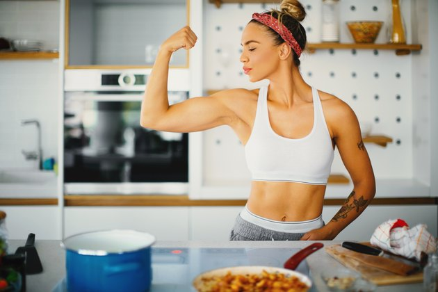 Woman in gym clothes flexing in kitchen