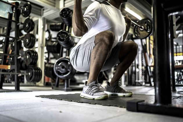 Man doing squat exercises in gym