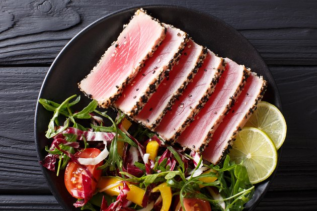 Top view of seared tuna steak, sliced and served with lime and a fresh salad