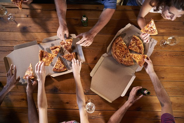 Overhead shot of friends at a table sharing take-away pizzas
