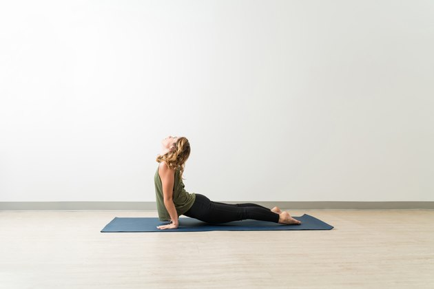 Woman practicing Upward Facing Dog pose on yoga mat