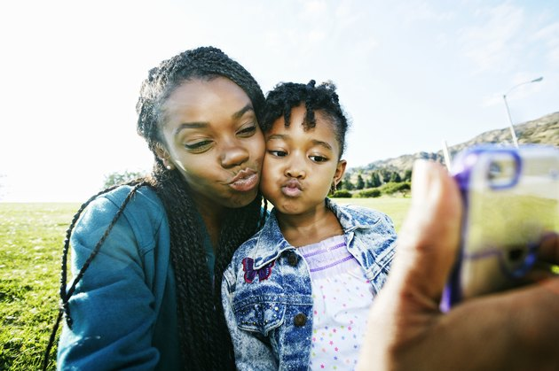 mother and daughter taking selfie outdoors