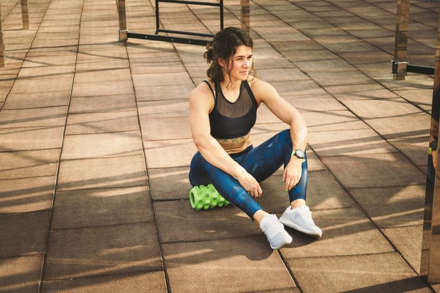 theme sport and rehabilitation sports medicine. Beautiful strong slender Caucasian woman athlete sits next foam roller green field street workout to remove the pain, stretch and massage muscles