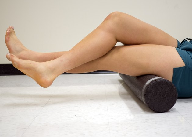 Varsity athlete using a foam roller to release her tight muscles