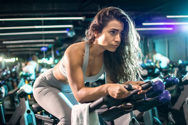 Beautiful fit woman cycling during workout on stationery bike for burning calories in the  studio.