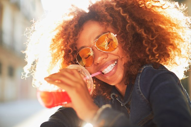 Beautiful young woman with afro drinking a pink drink