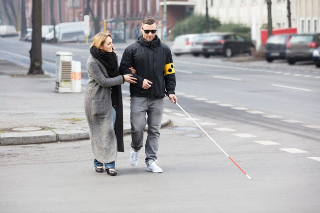 Woman Assisting Blind Man On Street.