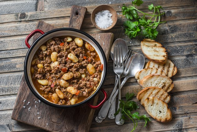 Cannellini beans beef slow-cooker stew on the wooden table, top view. Autumn, winter seasonal, healthy comfort food