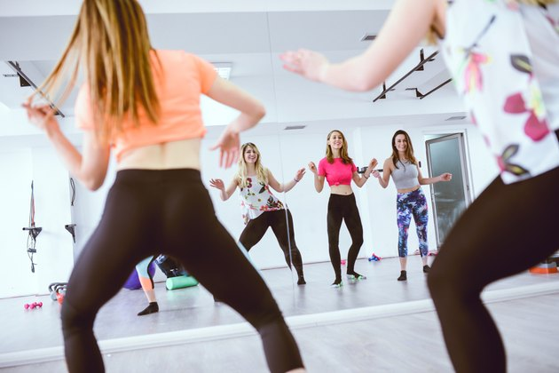 Group of Cute Smiling Females Training belly dancing in front of the Mirror in Gym