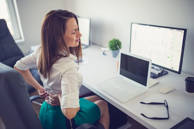 A woman sitting at her desk and holding her back in pain