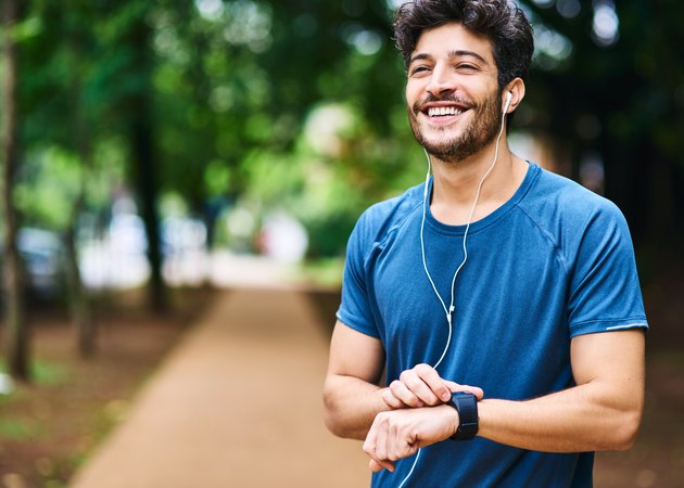 A smiling man wearing headphones and checking his smartwatch after a jog in the park