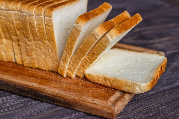 White bread sliced with slices on a wooden background for foods high in sodium