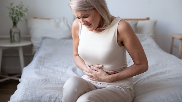 Woman holding belly, suffering from pain and thinking about foods to avoid with an upset stomach