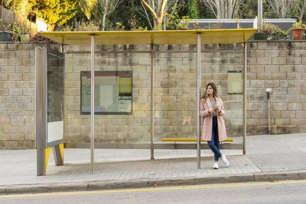 Young woman with cell phone waiting at bus stop