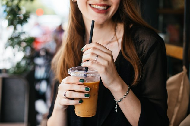 A smiling woman holding an iced coffee with a plastic straw