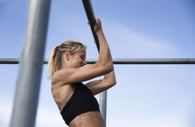 woman doing pull-ups outside