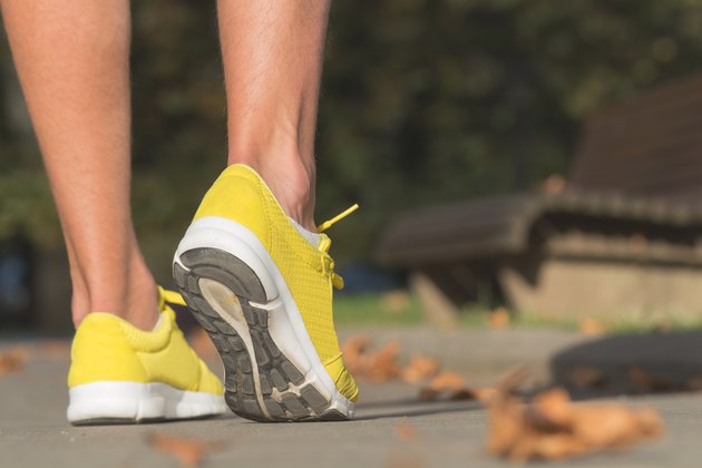 Detail of a running man's shoes / sneakers in the park.
